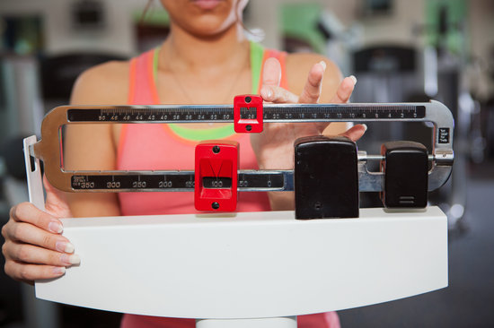 Gym: Woman Checks Weight on Traditional Scale