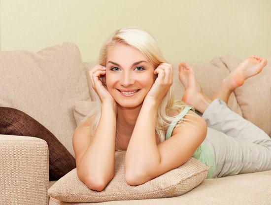 Happy Young Woman Lying on Sofa