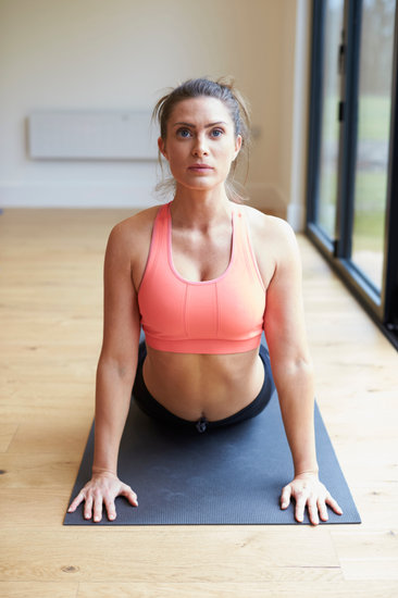 Mature Woman Exercising on Mat in Gym