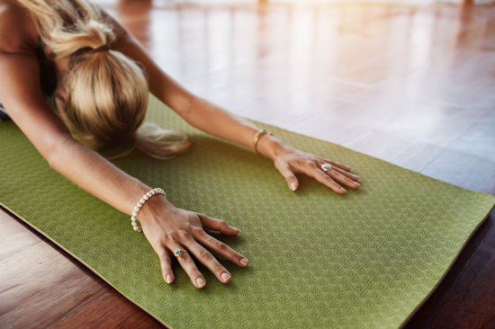 Female Doing Stretching Workout on Exercise Mat