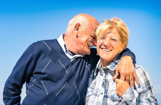 Happy senior couple in love during retirement - Joyful elderly lifestyle with man whispering and smiling with her wife