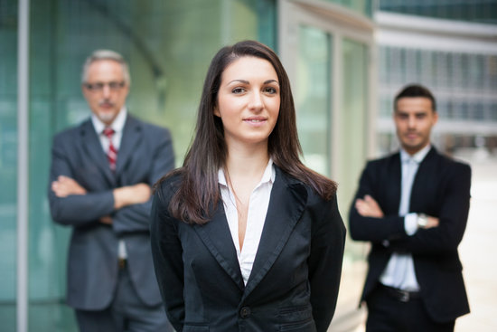 Businesswoman in Front of a Group of Colleagues