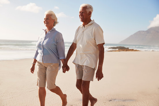 Senior Retired Couple Walking along Beach