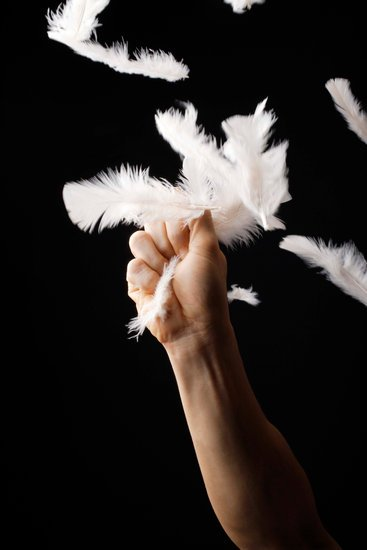 Hand gripping bunch of feathers