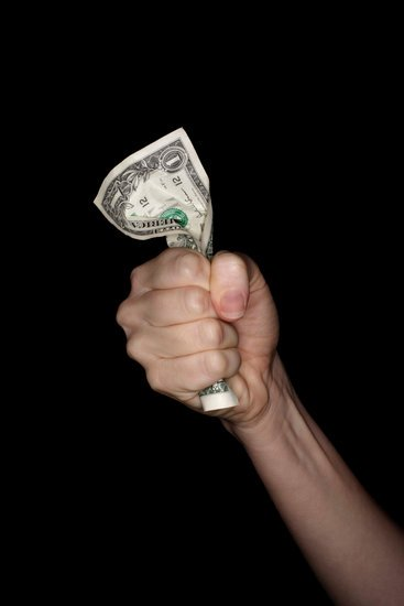 Hand gripping dollar bill