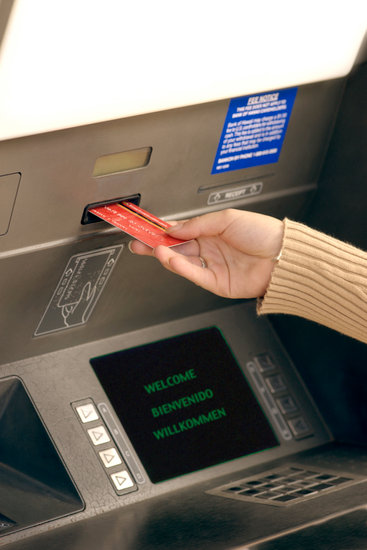 Woman inserting card into ATM machine