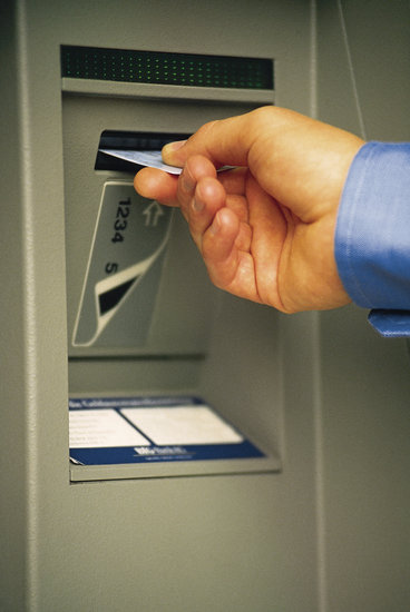 Hand inserting debit card being into ATM machine