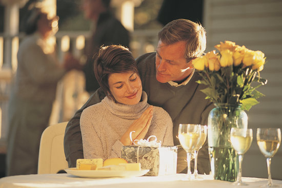 Man giving woman gift at romantic dinner