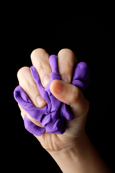 Hand gripping purple clay
