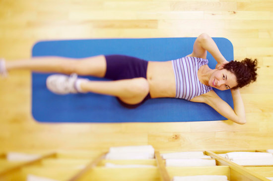 Woman lying on floor mat exercising