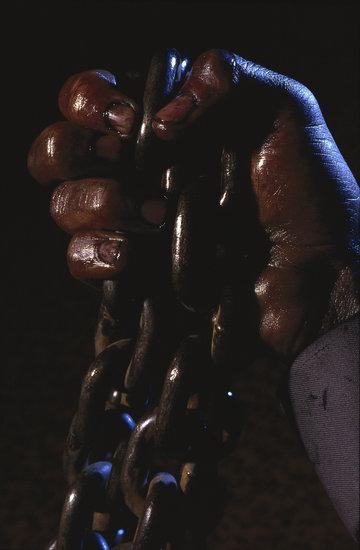 Man's hand gripping chains