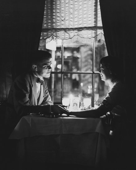 ROMANTIC DINNER / COUPLE HOLDING HANDS OVER TABLE BY CANDLELIGHT