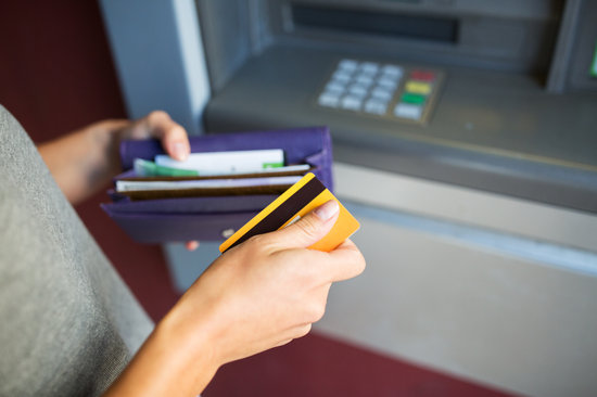 Hands with Money and Credit Card at Atm Machine