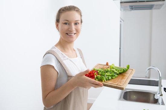 Jolly Young Woman Showing Cut Fresh Bell Pepper