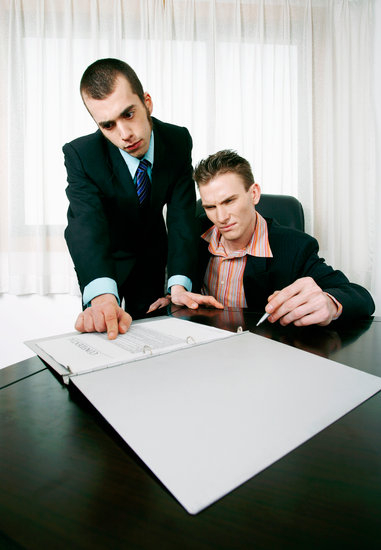 Businessman and his assistant reading through a contract