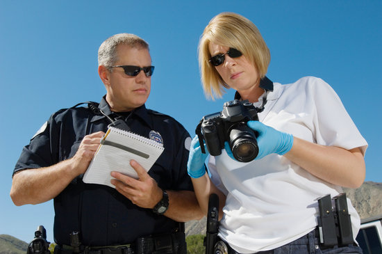 Police officer and investigator with camera