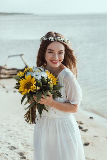 373b942656 beautiful happy girl in white dress holding sunflowers on beach
