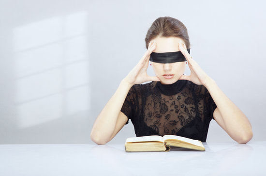 Woman with blindfold trying to read and understand foreign book.