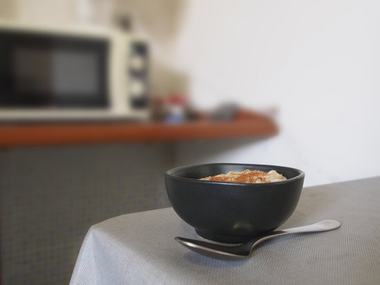 Organic  Hot Porridge in Brown Bowl on Kitchen Table. Defocussed Background. with Cinnamon and Spoon. Whole Grain Oats.