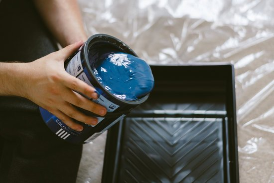 Person Holding Can of Blue Paint