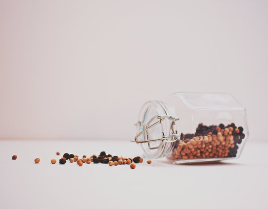 Black and Brown Peppercorns Spilling from Glass Jar