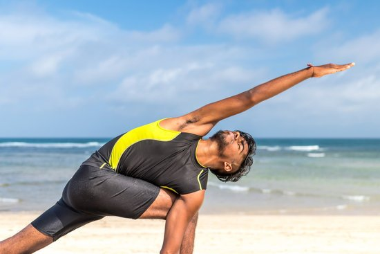 Man in Yellow and Black Tank Top Doing Exercise on Seashore at Daytime