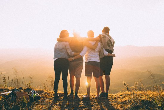 Four Person Standing on Cliff in Front of Sun