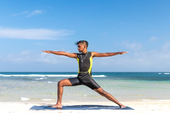 Man in Sleeveless Wet Suit Doing Some Aerobics at the Beach