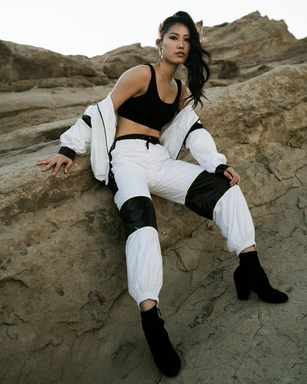 Woman Wearing Sports Bra and Pants While Leaning on Rock