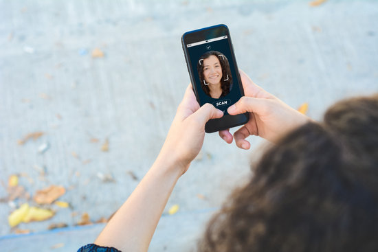 Woman Unlocking Smartphone Using Facial Recognition Technology
